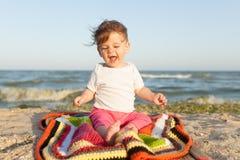Pequeño niño que se sienta en una manta coloreada en la costa alegre y feliz fotografía de archivo libre de regalías