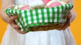 Pequeño niño que sostiene la cesta adornada con el huevo de Pascua antes de la cámara, celebración metrajes