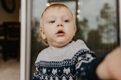 Pequeño niño rubio adorable lindo del niño que ríe, divirtiéndose, y haciendo caras tontas afuera en casa en el pórtico defendido fotografía de archivo