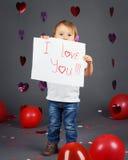 Pequeño niño rubio caucásico blanco adorable del muchacho en estudio con los corazones y los globos rojos en fondo gris Fotos de archivo libres de regalías