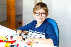 Pequeño niño rubio con los vidrios del ojo que juegan con las porciones de bloques plásticos coloridos imagenes de archivo