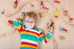 Pequeño niño rubio que juega con los trenes de ferrocarril de madera interiores Fotografía de archivo
