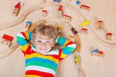 Pequeño niño rubio que juega con los trenes de ferrocarril de madera interiores Imagen de archivo