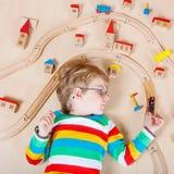 Pequeño niño rubio que juega con los trenes de ferrocarril de madera interiores Imagen de archivo libre de regalías