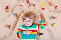 Pequeño niño rubio que juega con los trenes de ferrocarril de madera interiores Foto de archivo libre de regalías