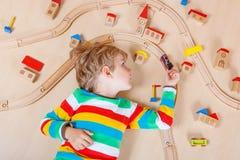 Pequeño niño rubio que juega con los trenes de ferrocarril de madera interiores Fotos de archivo libres de regalías