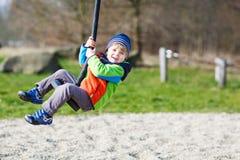Pequeño niño sonriente de dos años que se divierten en el oscilación en DA fría Fotos de archivo