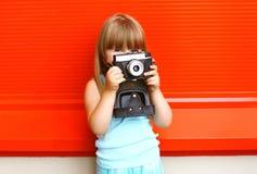 Pequeño niño sonriente de la muchacha con la cámara retra vieja del vintage Foto de archivo