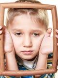Pequeño niño triste del muchacho que enmarca su cara Fotografía de archivo libre de regalías