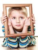 Pequeño niño triste del muchacho que enmarca su cara Imagen de archivo