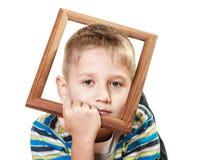 Pequeño niño triste del muchacho que enmarca su cara Imagenes de archivo