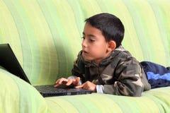 Pequeño niño y computadora portátil Imagen de archivo libre de regalías