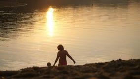 Pequeño niño y grandmom que van al mar durante puesta del sol hermosa en tiempo de vacaciones feliz Imagenes de archivo