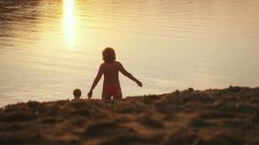Pequeño niño y grandmom que van al mar que lleva a cabo las manos durante tiempo de vacaciones feliz de la puesta del sol hermosa Foto de archivo libre de regalías