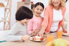 Pequeño nieto con la hermana que mira en los huevos con las salchichas y los tomates en la placa fotografía de archivo