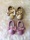 Pequeño oro del bebé y zapato color de rosa en el fondo mullido blanco imagenes de archivo