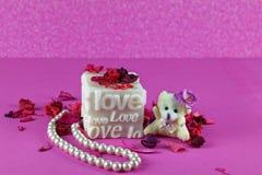 Pequeño oso de peluche con la caja del amor Fondo rosado fotografía de archivo libre de regalías