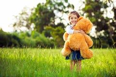 Pequeño oso de peluche lindo de la explotación agrícola de la muchacha Imagenes de archivo