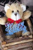Pequeño oso de peluche marrón con la muestra del feliz cumpleaños imagen de archivo libre de regalías
