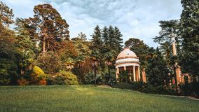 Pequeño pabellón con las columnas al aire libre en un jardín enorme del verano foto de archivo