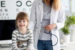 Pequeño paciente lindo sonriente que obra recíprocamente con el doctor de sexo femenino foto de archivo