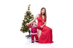 Pequeño Papá Noel lindo que presenta en el estudio cerca de árbol del Año Nuevo con la mamá Foto de archivo