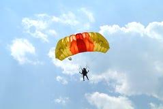 Pequeño paracaidista con el paracaídas rojo anaranjado del yelow colorido en la competencia que se lanza en paracaídas fotografía de archivo