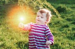 Pequeño paseo feliz de la niña pequeña al aire libre en un día soleado que sostiene la flor Tiempo de primavera, hierba verde imagenes de archivo