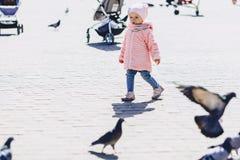 pequeño paseo lindo del bebé en cuadrado con los pájaros Imagenes de archivo