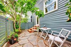 Pequeño patio trasero cercado con el piso y las sillas de piedra imagen de archivo libre de regalías