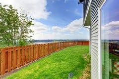 Pequeño patio trasero cercado de una casa azul grande Con la hierba jardín llenado fotografía de archivo