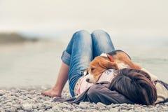 Pequeño perrito del beagle que miente en su pecho del dueño en el lado de mar fotografía de archivo