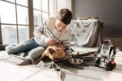 Pequeño perro que come de la manta Foto de archivo