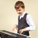 Pequeño pianista del principiante en un traje que juega el piano digital Imagen de archivo