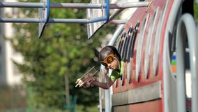 Pequeño piloto con el equipo del aviador que juega con el juguete plano de madera en ventana plana almacen de video
