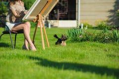 Pequeño pintor del perro, del perrito y de la muchacha fotos de archivo