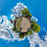 Pequeño planeta verde con los árboles, los cluds blancos y el cielo azul suave Planeta minúsculo del parque de atracciones ángel  foto de archivo