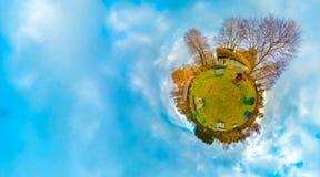 Pequeño planeta verde con los árboles y colmenar, nubes blancas y cielo azul suave Planeta minúsculo con la naturaleza en el otoñ imágenes de archivo libres de regalías