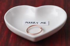 Pequeño platillo de cerámica en la forma de un corazón con un anillo y una nota foto de archivo libre de regalías