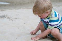 Pequeño playind del niño pequeño con la arena Foto de archivo libre de regalías