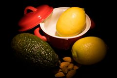 Pequeño pote, limones, aguacate, almendras, aún vida Imagen de archivo libre de regalías