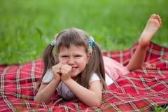 Pequeño preschooler irritado de la muchacha que miente en la tela escocesa Foto de archivo libre de regalías