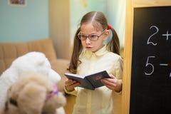 Pequeño profesor en vidrios La chica joven hermosa está enseñando a los juguetes Foto de archivo libre de regalías