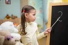 Pequeño profesor La chica joven hermosa está enseñando a los juguetes en casa encendido Foto de archivo
