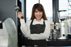 Pequeño propietario de negocio que se coloca en el contador en cafetería hembra Imagenes de archivo