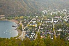 Pequeño pueblo con los barcos al lado de un lago en las montañas foto de archivo