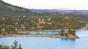 Pequeño pueblo con los barcos al lado de un lago en las montañas imagenes de archivo