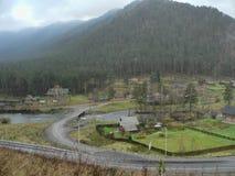 Pequeño pueblo en el valle entre las montañas Foto de archivo libre de regalías