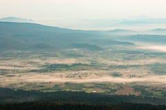 Pequeño pueblo en el valle rodeado por las montañas Foto de archivo libre de regalías