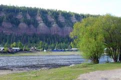 Pequeño pueblo en la orilla del río Paisaje de la tarde del verano Foto de archivo